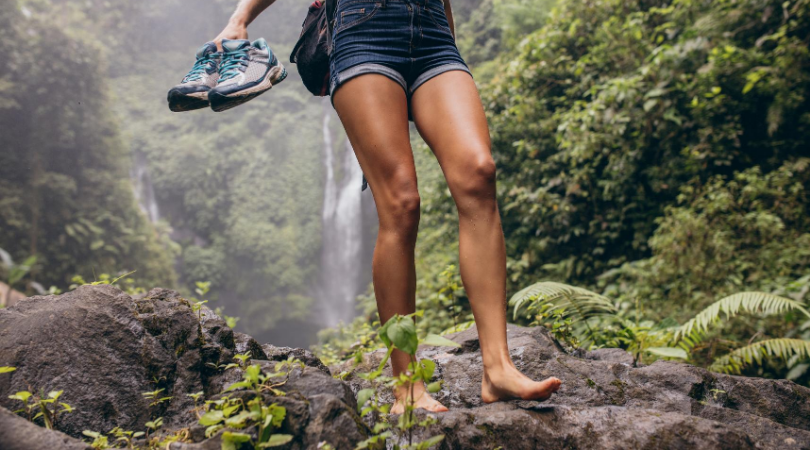 Runner walking in bare feet while holding shoes